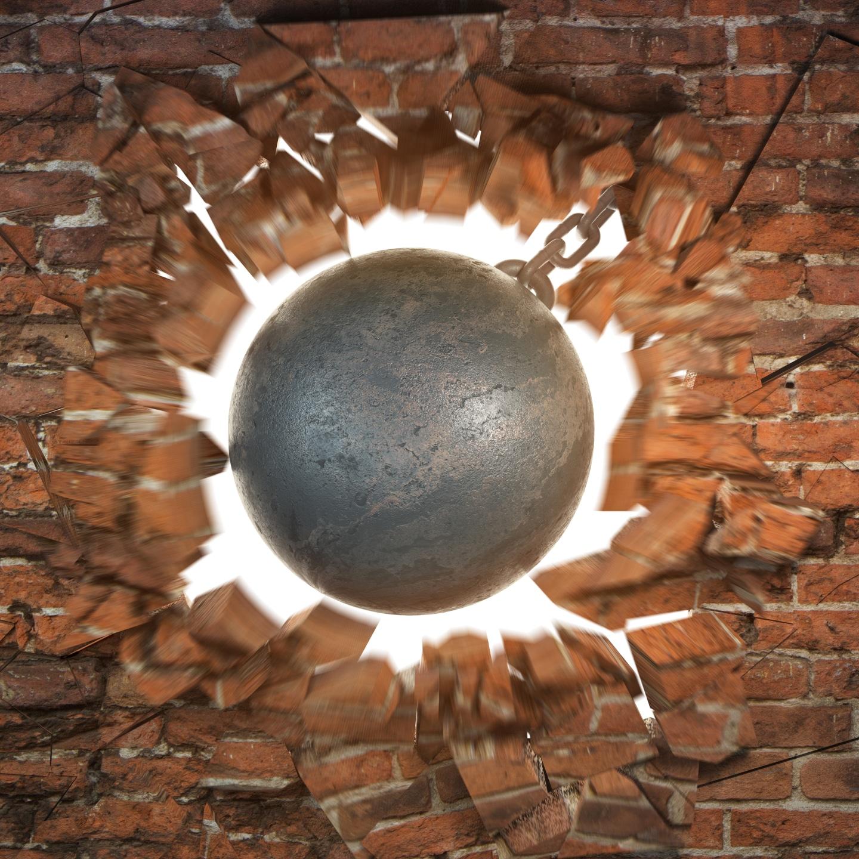 Wrecking ball destroying the brick wall.